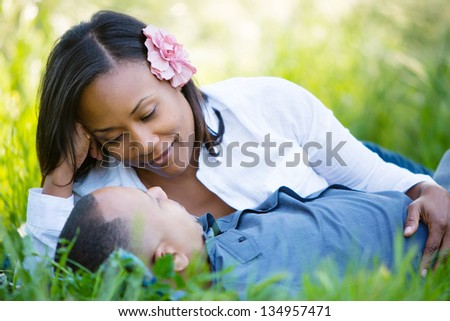 Pretty black woman lying in the grass with her boyfriend - stock photo