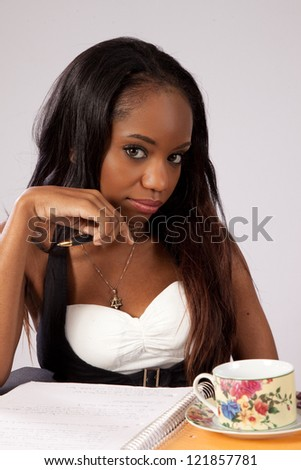 Pretty black woman thinking with a pen and paper, with eye contact and serious expression