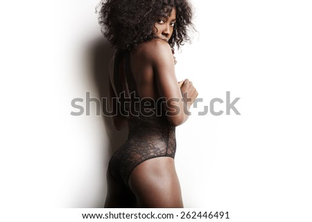 pretty black woman watching back to camera on a white background - stock photo