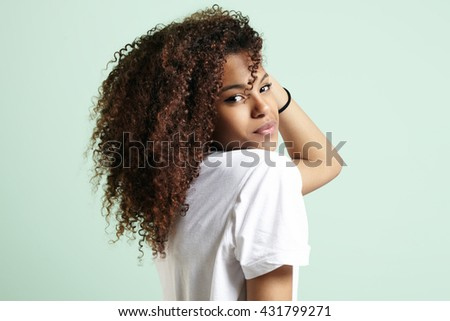pretty black woman with a curly hair watching at camera from the back