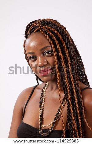 Pretty black woman with dreadlocks, looking at the camera with a serious and and thoughtful but  friendly expression - stock photo