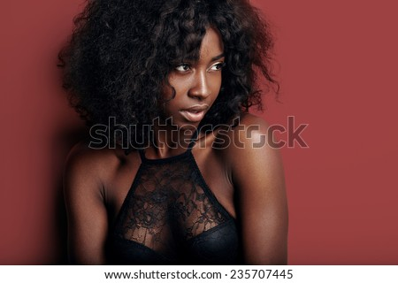 pretty black woman with ideal skin on a black background - stock photo
