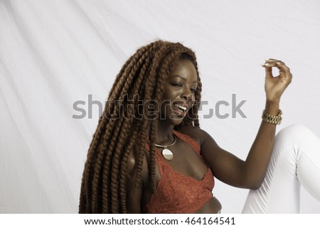 Pretty Black woman with long dreadlocks, sitting  and smiling with joy
