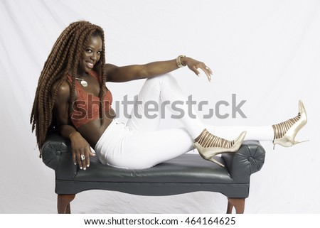 Pretty Black woman with long dreadlocks, sitting on a bench and smiling with joy