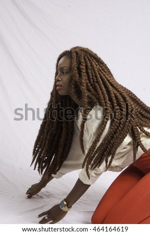 Pretty Black woman with long dreadlocks, sitting on the floor and looking thoughtful