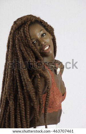 Pretty black woman with long dreadlocks, smiling at the camera