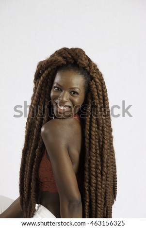 Pretty black woman with long dreadlocks smiling with pleasure at the camera