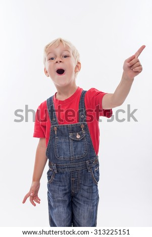 Pretty blond boy is standing and smiling. She is pointing his finger sideways and opening his moth with surprise. Isolated on background - stock photo