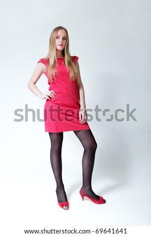 Pretty blond-brown lady wearing fashionable pink dress. Fresh new young face. Studio shot, uniform background. - stock photo