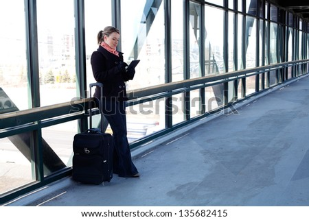 Pretty Blond Business Woman Using A Tablet Computer While Traveling With Her Rolling Luggage At The Airport - stock photo