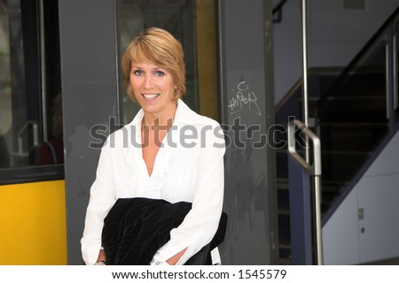 Pretty blond businesswoman getting on the train to work - stock photo