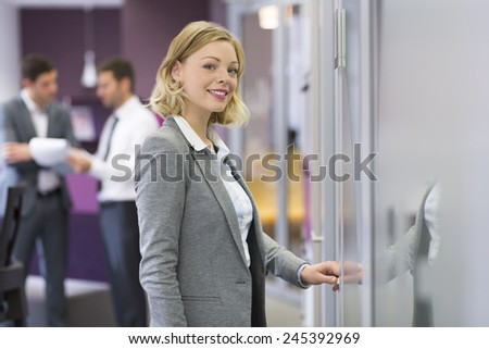 Pretty blond businesswoman open de door in modern office. Concept - stock photo