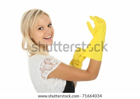 Pretty blond cleaning lady putting on yellow latex gloves - stock photo