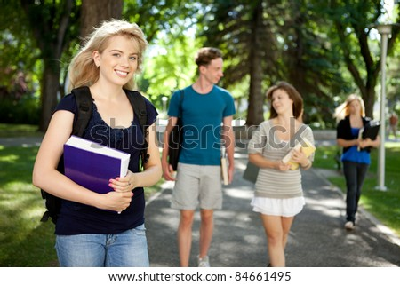 Pretty blond college girl looking at camera with friends in background - stock photo