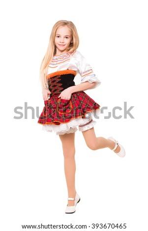 Pretty blond girl in a checkered dress posing on one leg. Isolated - stock photo