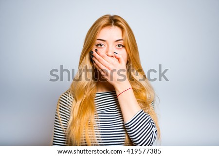 Pretty blond girl in shock closing mouth with hands - stock photo