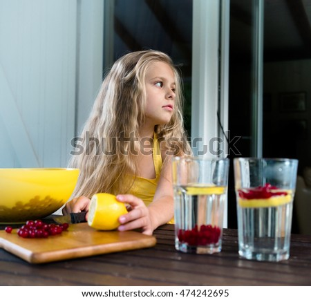 Pretty blond girl is preparing berry drink from a lemon and red currant