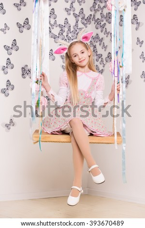 Pretty blond girl wearing goat costume posing on the swing - stock photo
