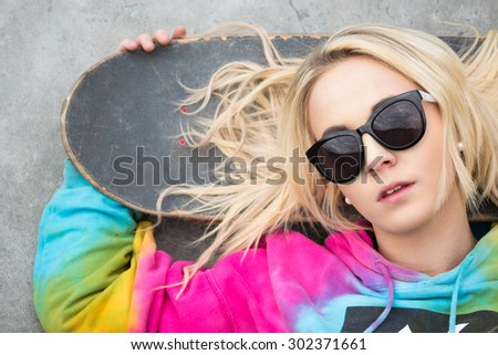 Pretty blond girl with skateboard - stock photo