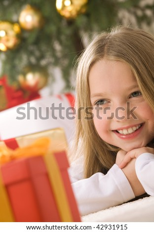 Pretty blond hair girl smiling. Red gift box with gold ribbon on first plan. Christmas tree with golden glass-balls in background - stock photo
