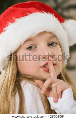 Pretty blond hair girl with santa hat. Christmas tree in background - stock photo