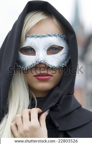 pretty blond hidding her face with white mask and black hood - stock photo