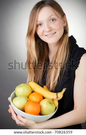 Pretty Blond Holding Healthy Fruit with Grey Background - stock photo