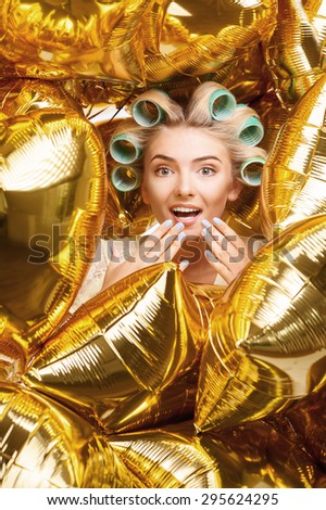 Pretty blond housewife is surrounded by a great amount of colored balloons. She is surprisingly happy. She raises hand to her moth with admiration - stock photo