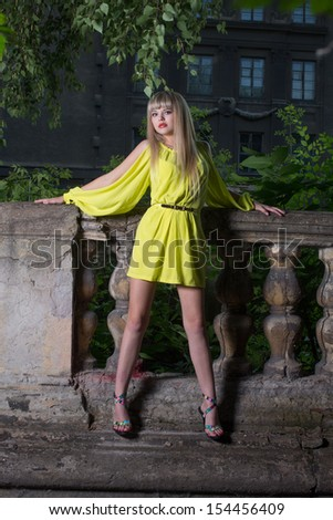 Pretty blond in a short yellow dress stands against the background of the old castle