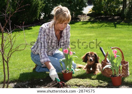 Pretty blond lady enjoying her garden at spring time. - stock photo