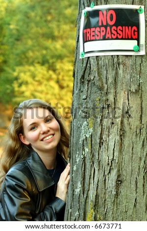 """Pretty blond leaning on a tree with """"No Trespassing"""" sign - stock photo"""