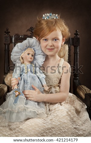 Pretty blond little girl in the old fashioned interior with a doll 