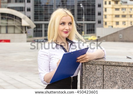 Pretty blond manager hold tablet with abstract graphics and documents outdoors.  Business person.