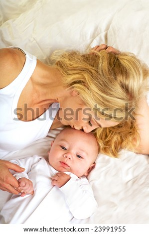 Pretty Blond Mother kissing her baby