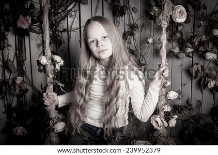 pretty blond preteen girl sitting with flowers - stock photo