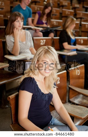 Pretty blond student in lecture theater looking at camera - stock photo