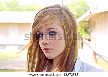 Pretty blond teen girl by a school stares into the camera in an outdoor headshot.