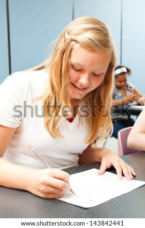 Pretty blond teen smiles confidently while taking a test. - stock photo