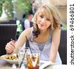 Pretty blond teenage girl dining at a sunny outdoor cafe. - stock photo