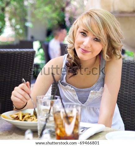 Pretty blond teenage girl dining at a sunny outdoor cafe.