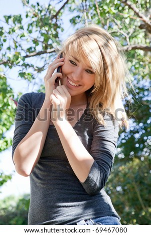 Pretty blond teenage girl talking on cell phone (mobile phone) outdoors on a sunny day. - stock photo