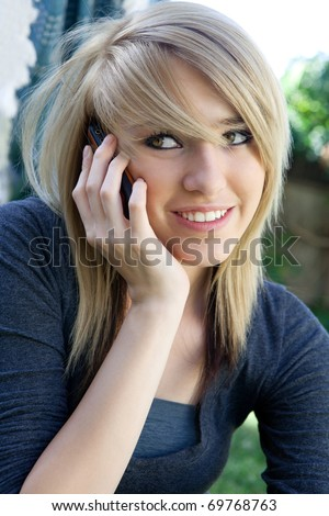 Pretty blond teenage girl talking on mobile cell  phone outdoors on a sunny day. - stock photo