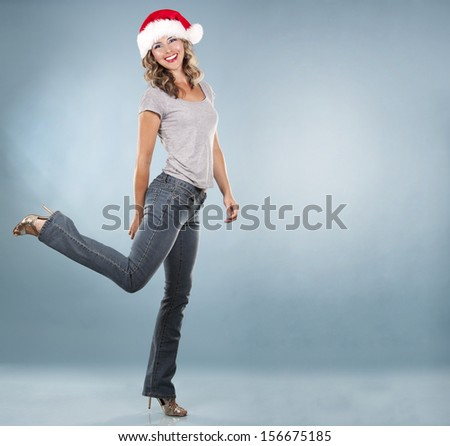 pretty blond wearing christmas hat on light blue background