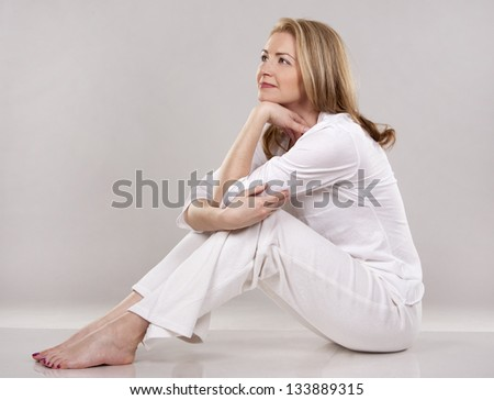 pretty blond wearing white outfit on light background - stock photo