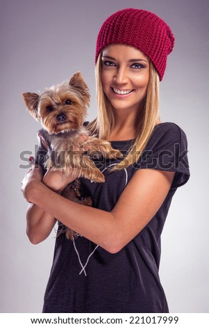 Pretty blond woman dressed in autumn with yorkshire terrier dog  - stock photo