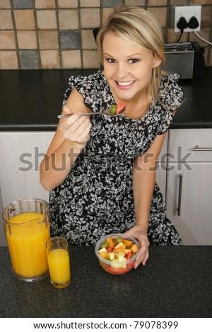Pretty Blond Woman Eating Breakfast - stock photo