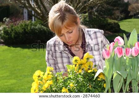 Pretty blond woman gardening outside. - stock photo