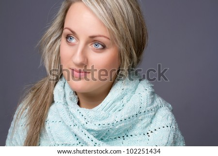 Pretty blond woman in a winter sweater over gray background