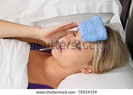 Pretty blond woman in bed with headache and thermometer in her mouth - stock photo