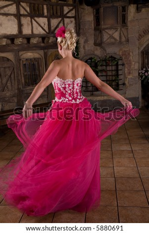 Pretty blond woman in party dress twirling around - stock photo